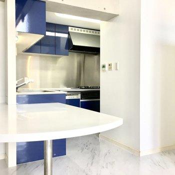 ブルーのL字キッチンには大きなカウンターと、、※写真は2階反転間取り・別部屋のものです