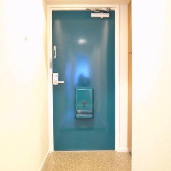 ターコイズブルーのドアは唯一の差し色。玄関もゆったりめです。