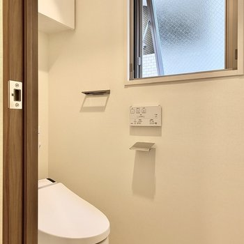 廊下に面したお手洗い。上部には戸棚がついています。