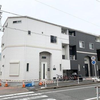 ツートンカラーの角地に建つ2階建てのアパートです。