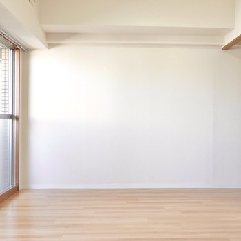 右奥にはキッチンが。正面の壁にはダイニングテーブルを置いて食卓に。 (※写真は9階の反転間取り別部屋のものです)