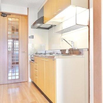 木目のパネルのキッチンは奥まった場所にあり、生活感を出しにくく。 (※写真は9階の反転間取り別部屋のものです)