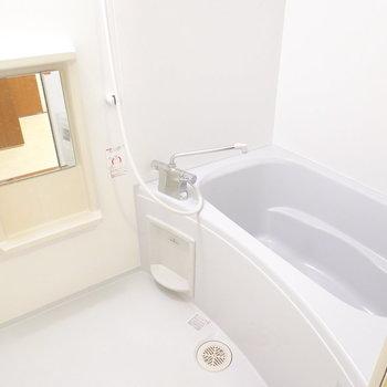 鏡付きのお風呂は浴槽が広く、ゆったりと疲れを癒せそうです。 (※写真は9階の反転間取り別部屋のものです)