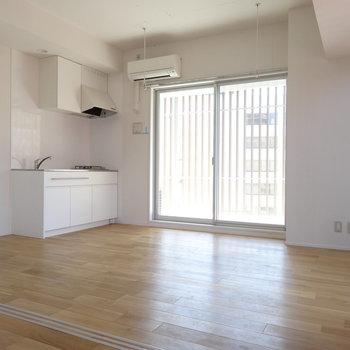 キッチン側にも窓。この無垢床気持いい〜(※写真は8階の同間取り別部屋のものです)