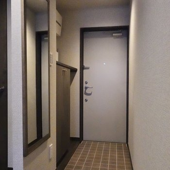 玄関にはラックと姿鏡が。身だしなみチェックはここでどうぞ。