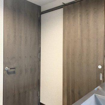 キッチン後ろの扉は、右の引き戸がサニタリー。左のドアは…