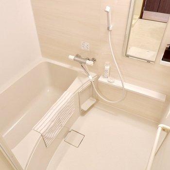 白が基調の浴室。鏡周りのラックが多く、多用途ですね。