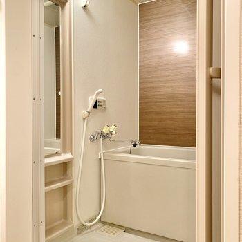 壁が木目調で優しい雰囲気の浴室は、追い焚き機能付き。