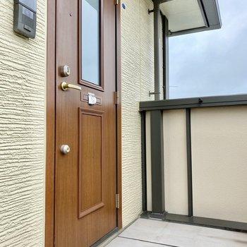 玄関前。ポストはドアに取り付けられています。