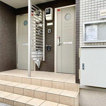 玄関前共用部。ゆったりとしていてドア横には傘掛けがありますよ。