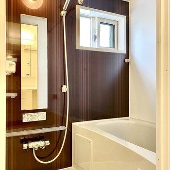 浴室。ダークブラウンの木目が映えるシックな空間です。