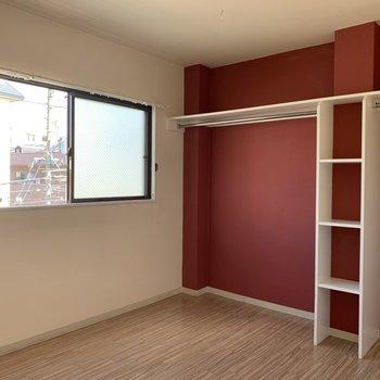 続いて、洋室のお部屋。赤色の壁に個性的なオープンクローゼットが特徴的