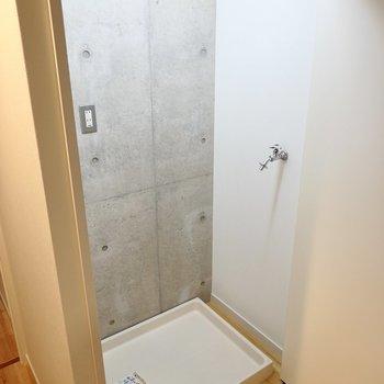 トイレの正面には折れ戸があり、中には照明に照らされた洗濯機置場が!