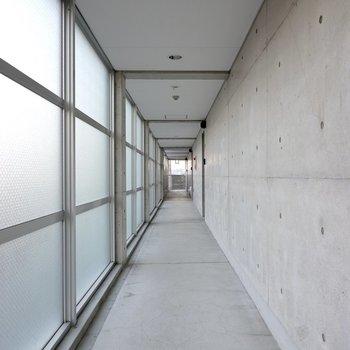玄関前の共用部は半透明の壁から光が注ぐ神秘的な空間。
