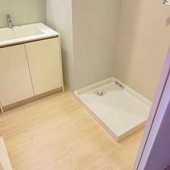 脱衣所は少しナチュラルな床で安らぎを。入って右手に洗濯機置場。