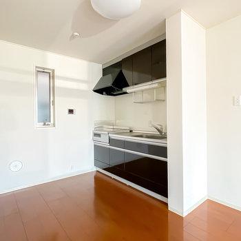 白い空間に黒いキッチンが映えます。冷蔵庫置き場は右に、家電用のスペースは左に。