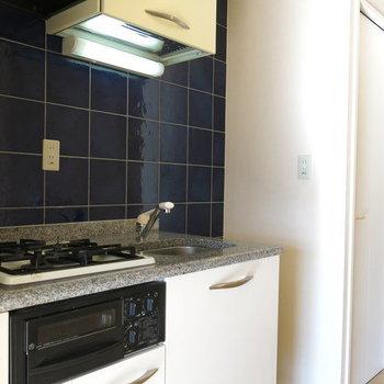 黒タイルが光るキッチンの前には収納棚つきです(※写真は9階の同間取り別部屋のものです)