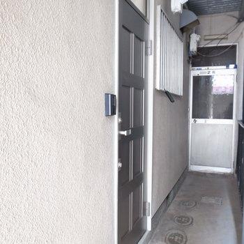 【共用部】階段下の通路の途中にお部屋の玄関があります。