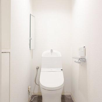スタイリッシュなフォルムのウォシュレット付きトイレ。手洗い器の左の壁には小さな鏡がついています。