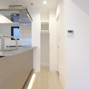 こちらはキッチンの前。右奥に脱衣所へのドア。正面は可動棚のあるオープン収納になっています。