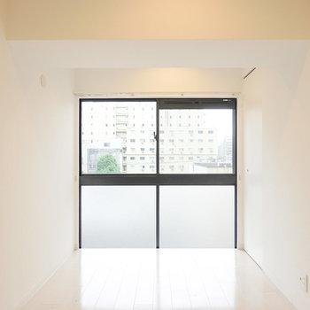 約7.9帖の洋室。窓に向かってストンと落ちる床がまるでインフィニティプールのような印象。