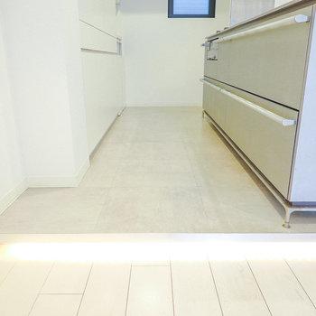 キッチンの床はモルタル調。LDから一段上がった配置と、床の隙間の間接照明はまるでドラマのセットのよう。