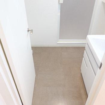 脱衣所はふたり同時に立てる広さ。こちらの床もキッチンと合わせたモルタル調。
