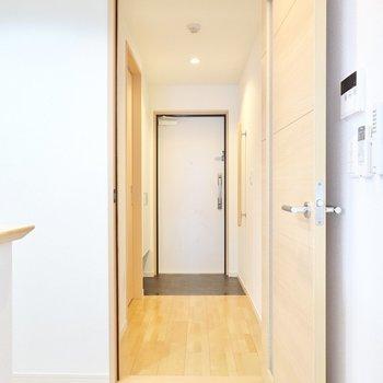 キッチン隣のドアから玄関へ。左手に脱衣所があります。