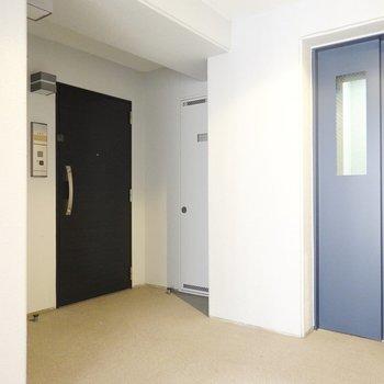 玄関はモノトーンでクールに。エレベーターを降りてすぐ隣のお部屋です。