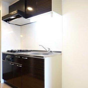 白い空間に黒いキッチンパネルが映えます。冷蔵庫置場は右側に。(※写真は2階の同間取り別部屋のものです)