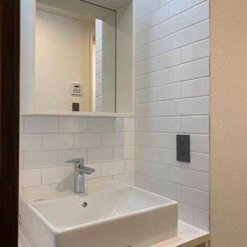かわいくて機能的な洗面台。鏡部分は棚になっていてメイク道具なども置けそう。