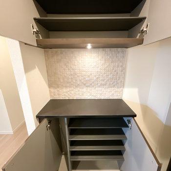 靴箱は1段に3足ほど入る横幅。真ん中のスペースはタイル張りで、照明も明るい!