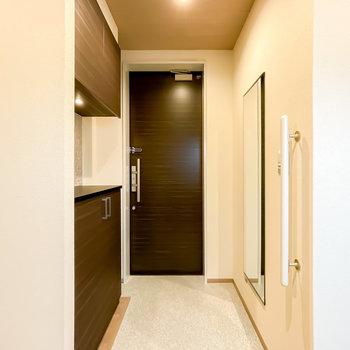 玄関はキッチンの対面側に。壁には靴も合わせてコーディネートのチェックができる姿見付き!