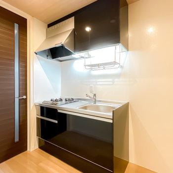 キッチンは建具とカラーを合わせたブラック。家電用のスペースは右側に。