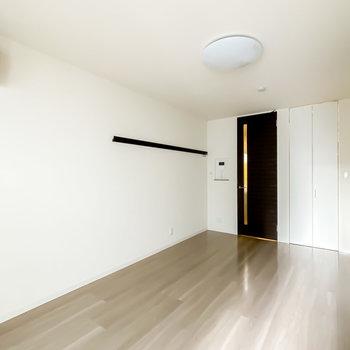 反対の壁にはフック付きのピクチャーレールも。右手の白い扉の中には……