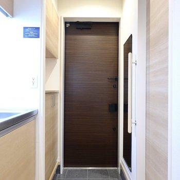 玄関はキッチンの隣に。ドアとタタキがクールな色味。