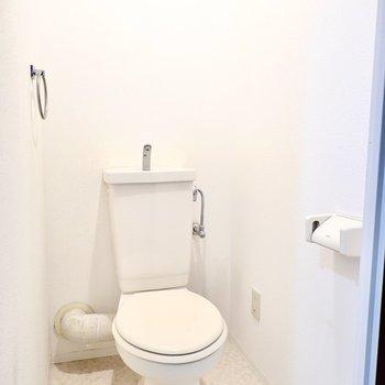 トイレもシンプルですが、どちらも清潔にされています。収納棚は扉の上に。