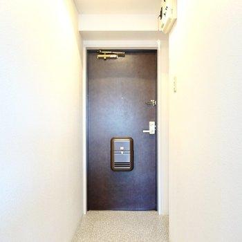 玄関は廊下の奥に。靴箱は右手の壁の窪みにすっぽり。