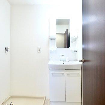 脱衣所に入って正面に棚付きの洗面台と洗濯機置場。