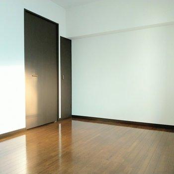 ベッドとテーブル。家具は最小限に。扉の先は…?(※写真は7階の同間取り別部屋のものです)