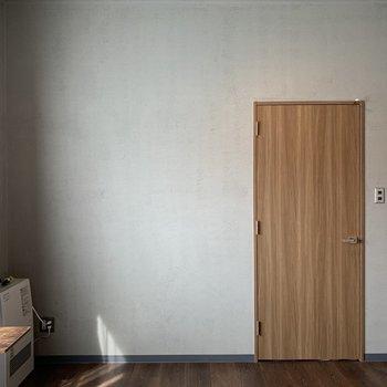 グレーの壁と木のドアで落ち着いた雰囲気に。