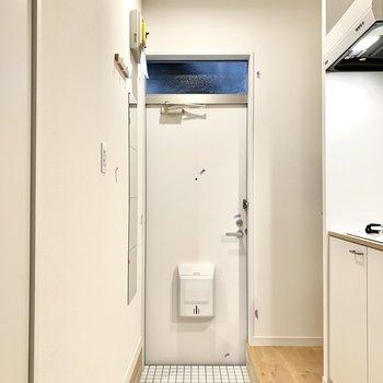 扉、玄関タイル、キッチンとすべて白で統一されています