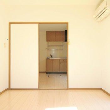 洋室はエアコン付き。引き戸を開ければキッチンがちらり。(※写真は清掃前のものです)
