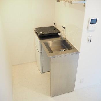 【2階】キッチンは置き型のIH。冷蔵庫も備え付けられています。※写真は同間取り別部屋のものです