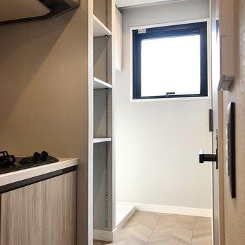 キッチンの奥に棚と洗濯機置き場が。
