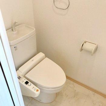 トイレは玄関近くに。ウォシュレット付き。上には棚もあります。(※写真は5階の同間取り別部屋、清掃前のものです)