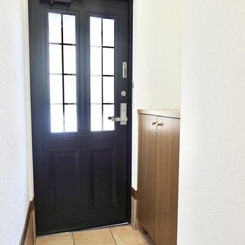 お部屋の最後は玄関を。タイルのタタキと黒いドアが素敵。