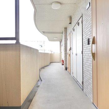 お部屋の前の共用部。木目調のドアが素敵。