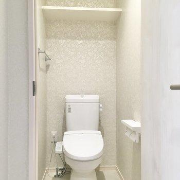 アクセントクロスがあしらわれたトイレ。ストックは後ろのラックへ。