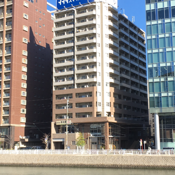 川の前にある大きな建物で、お部屋の前の歩道も整備されています。